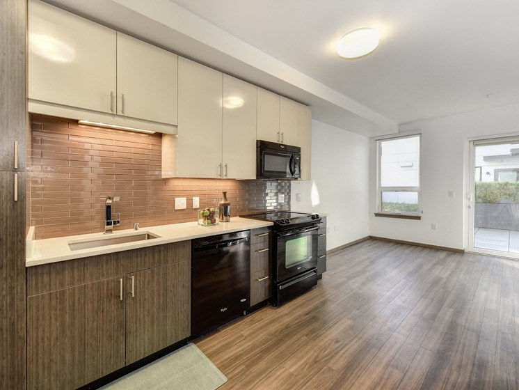 Luxury Apartment Community Open Kitchen with View of Living Room and Wood Inspired Floors