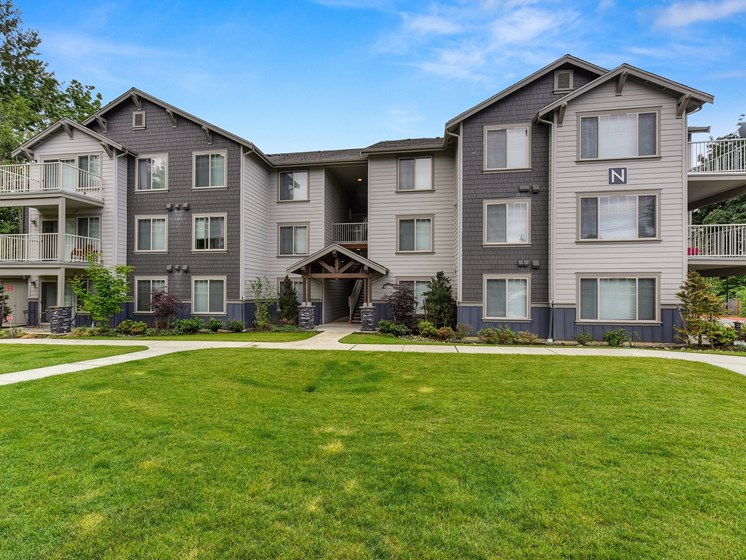 Front of Avaya Trails with Grass, Walking Path, Gray Apartment Exteriors