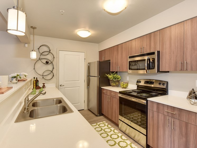 Model Kitchen with Sinks, Wood Inspired Floor, Sinks, Countertop, Oven, Wood Cabinets, Ceiling Lights