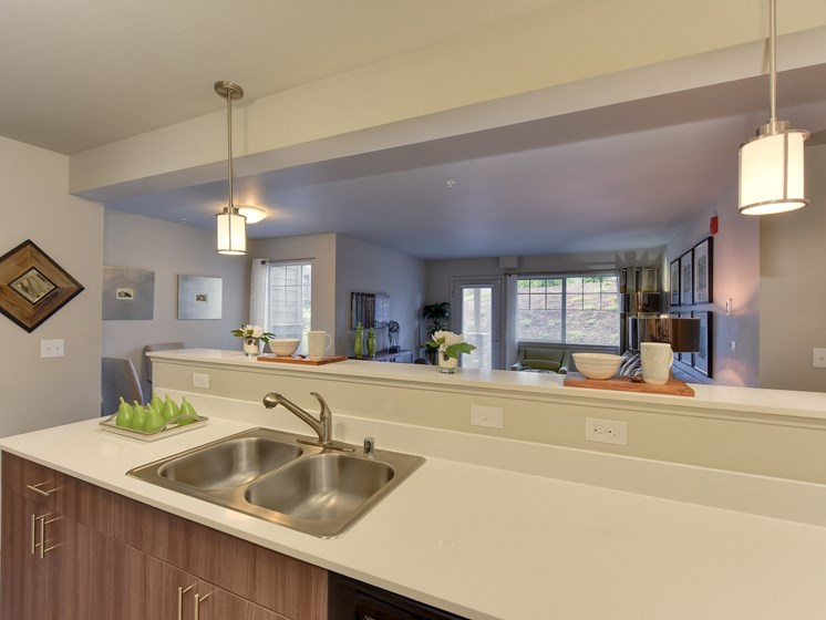 Model Kitchen with View of Living Room, Sink Counter Top, and Hanging Lights