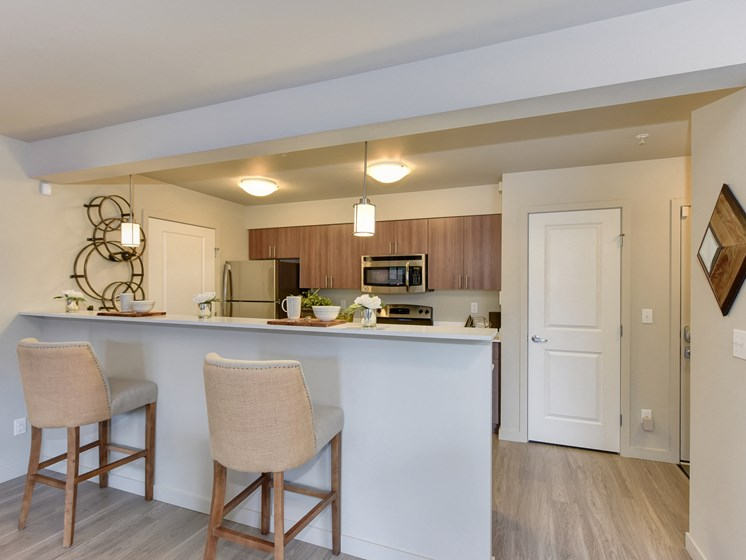 Model Kitchen with Counter,Stools, Hardwood Inspired Floor, Ceiling Lights, and Fridge/Freezer