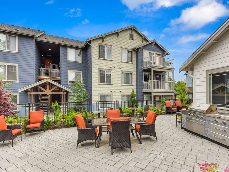 Outdoor Seating Area with Grill, Orange Chairs, Tile Inspired Floor, Blue Apartment Exterior