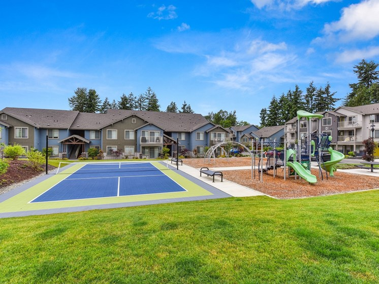 Tennis Courts and Playground, Wood Chip Floor, Grass, and Apartment Exteriors