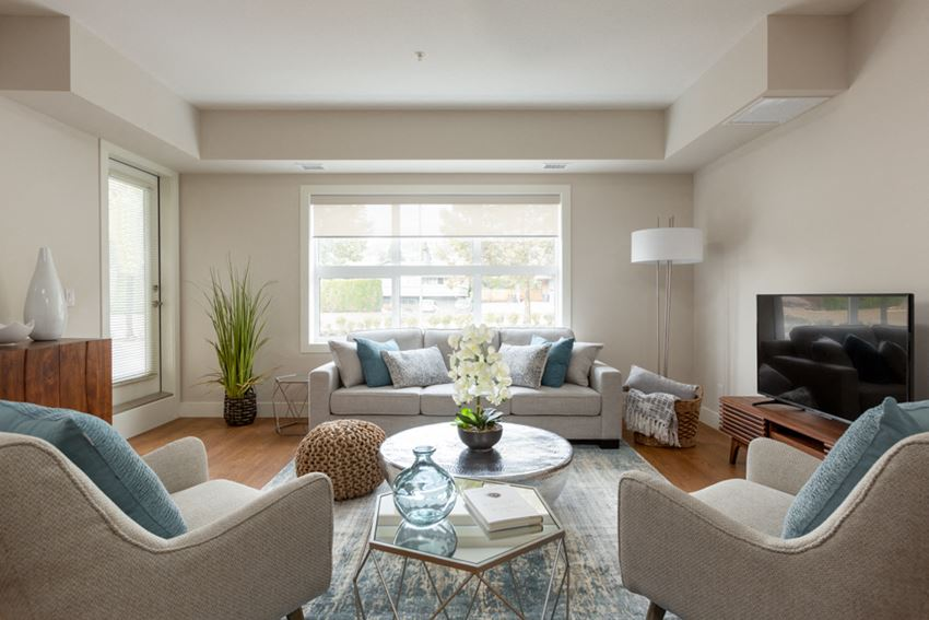 The Conservatory large, elegant living room with big window and hardwood flooring in Kelowna, BC