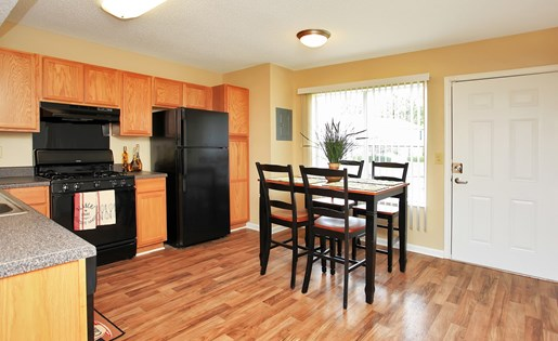 All black appliances, hardwood floors and sit-in dining