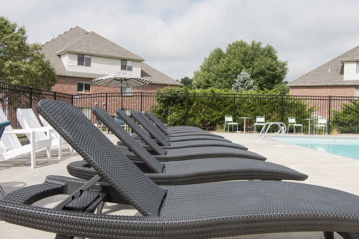Lounge chairs next to the swimming pool at Fountain Glen Apartments
