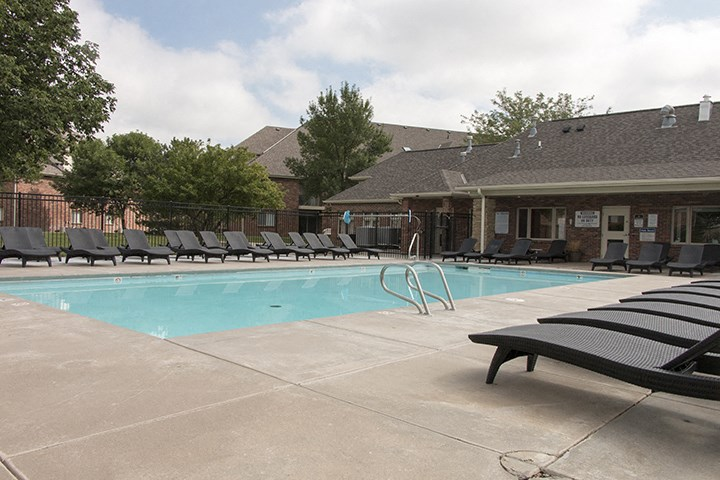 Exteriors-Fountain Glen spacious clubhouse next to swimming pool with lounge chairs lincoln NE