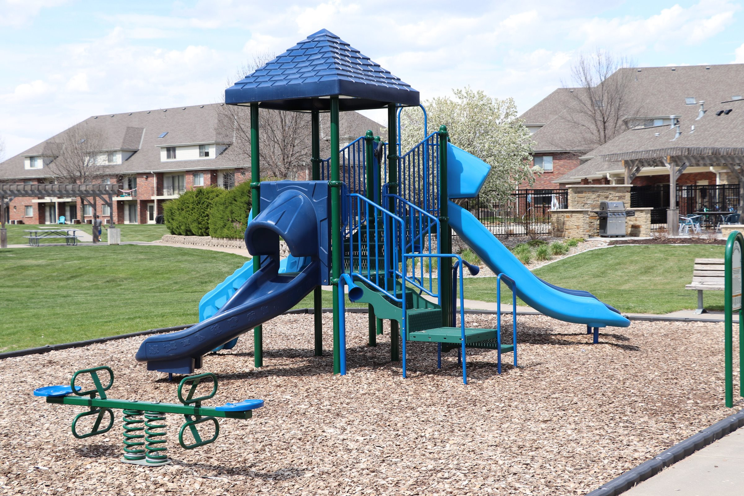 Children's playground with slides and a seesaw at Fountain Glen Apartments in Lincoln, NE