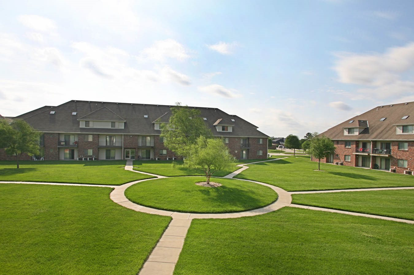 Spacious grounds with walking paths, lush green grass and trees, surrounded by brick apartment buildings at Fountain Glen Apartments in Lincoln, NE.