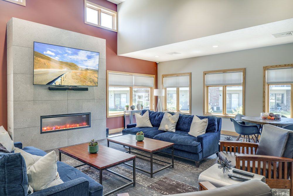 Spacious clubhouse with comfortable couches and chairs, tables, large TV, cozy fireplace, and lots of natural light coming in from the windows at Fountain Glen Apartments in Lincoln NE