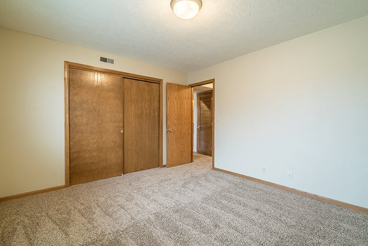 Spacious bedroom with closet space at Fountain Glen Apartments