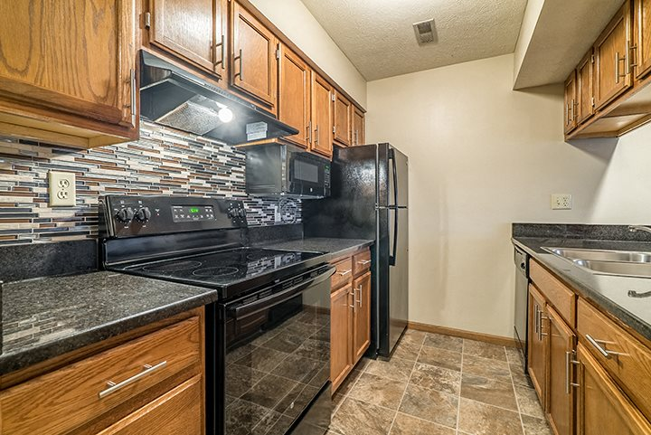 Renovated kitchen with updated appliances and dark wood cabinetry at Fountain Glen Apartments