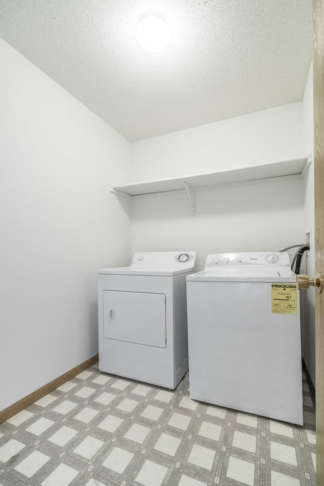 Interiors-Full-size washer and dryer in separated laundry room at Northridge apartments in Lincoln