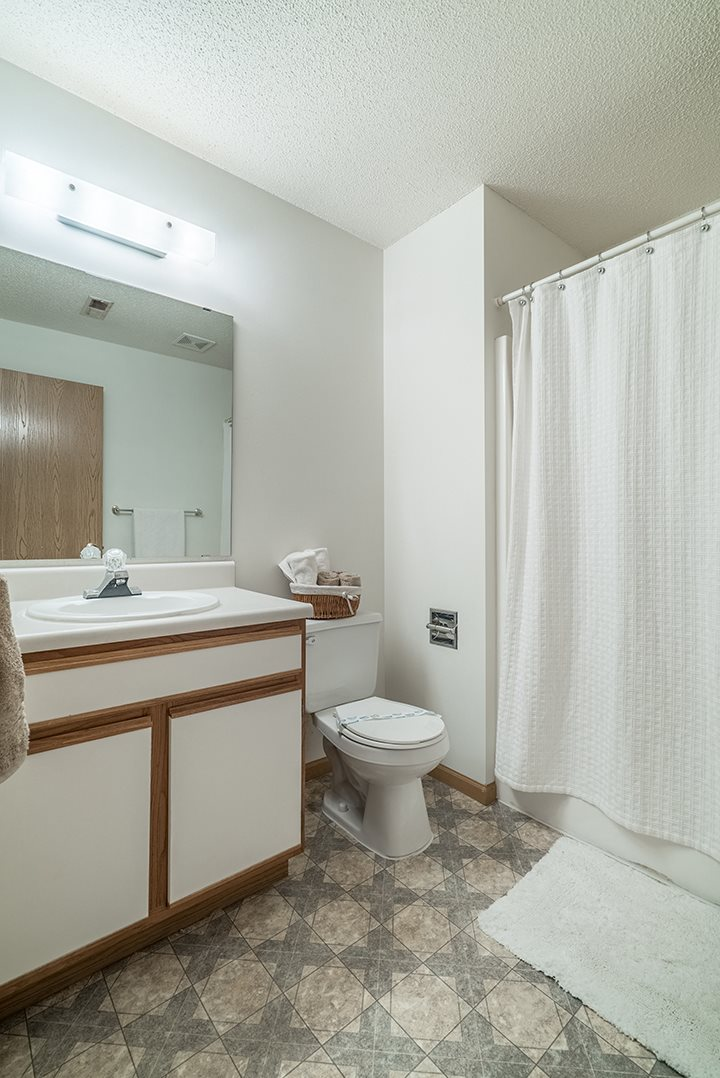 Bathroom with bright lighting and vanity at The Northbrook Apartment Homes, Lincoln, NE