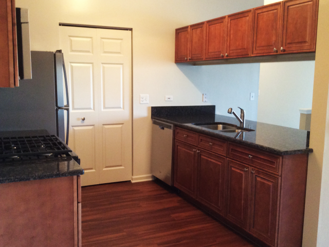 Black Countertops and Cherry Wood Cabinetry at HighPoint Community Apartments, Romeoville, IL, 60446
