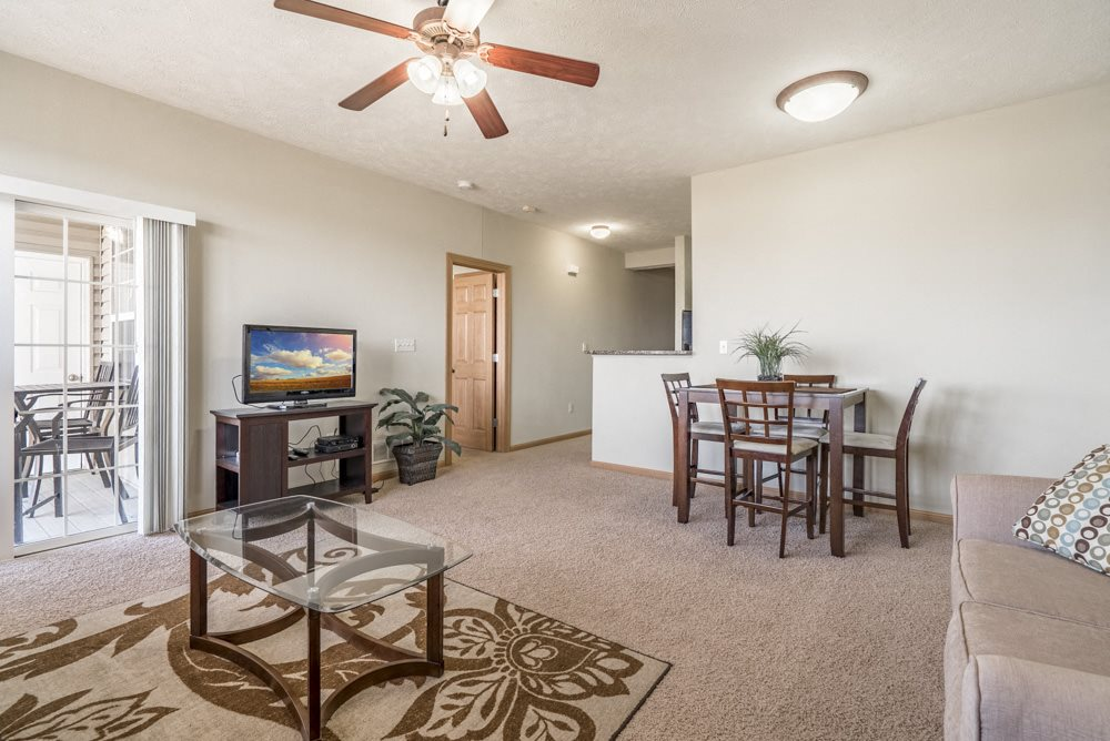 Villa living room with ceiling fan and walkout patio at Stone Ridge apartments in south Lincoln NE