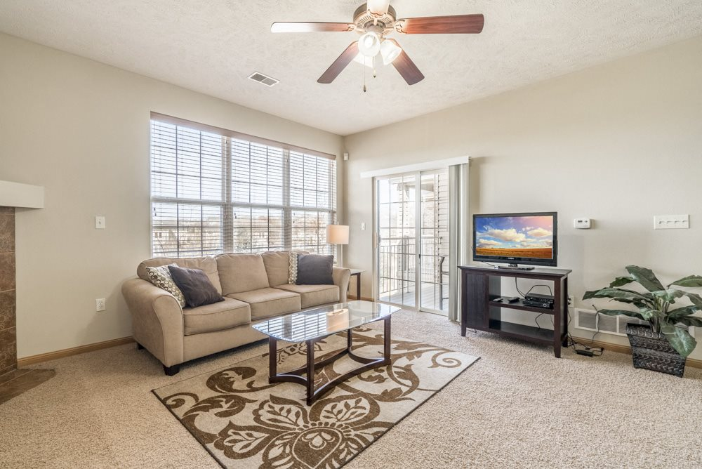 Living room with ceiling fan, patio and large windows in 1 bedroom apartment for rent at Stone Ridge Estates