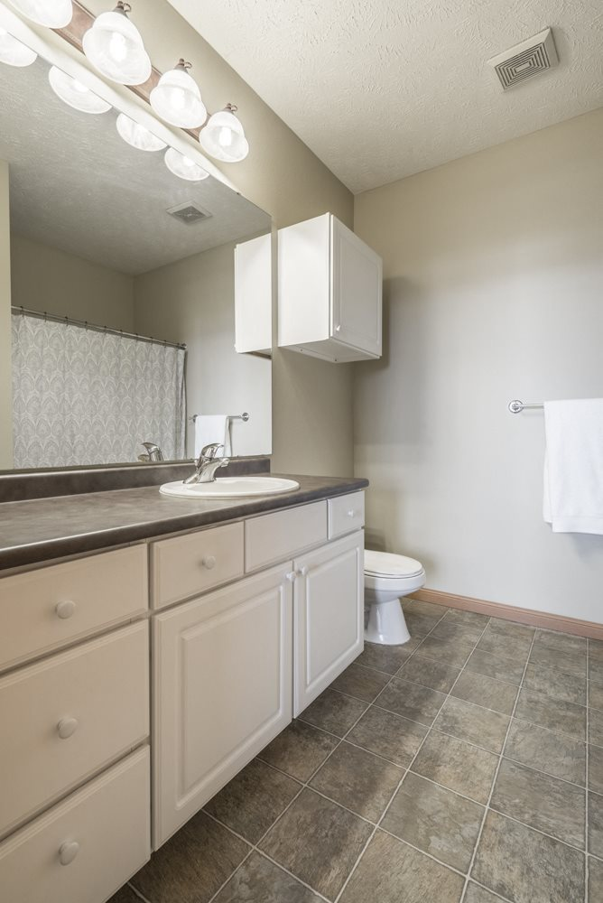 Updated bathroom with white cabinetry and lots of space at Stone Ridge Estates in Lincoln NE