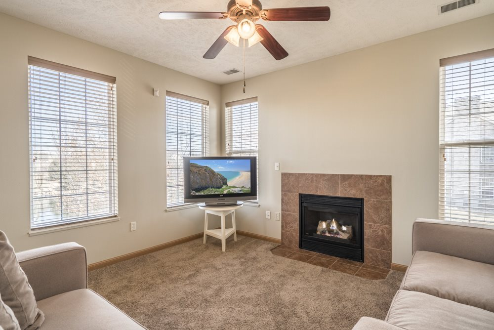 Living room with view of fireplace, ceiling fan and large windows