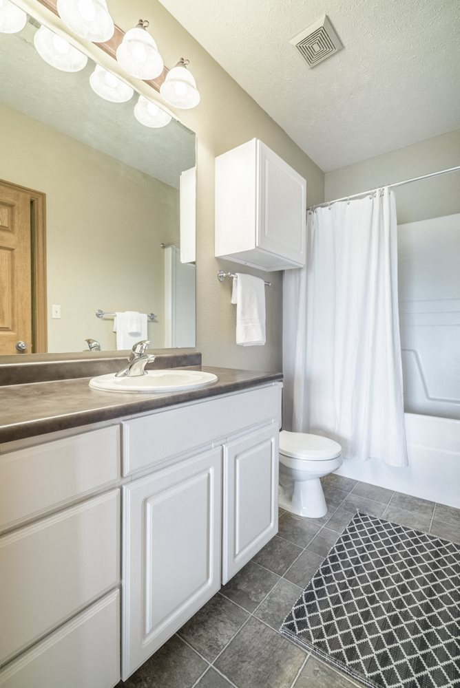 Bathroom with white cabinetry and bathtub at Stone Ridge townhomes in south Lincoln NE