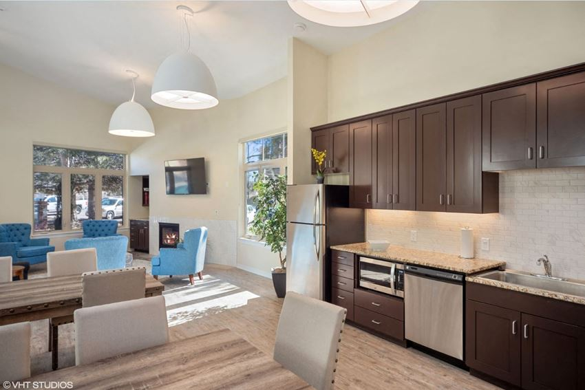 Club house with two seating area, one with arm chairs, fireplace, wall mounted TV, two long dining tables with  chairs and dark kitchen counters with stainless steel appliances with silver fixtures.