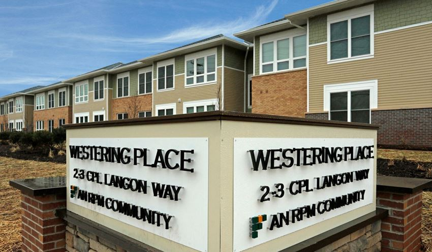 """Exterior of building with sign that read """"Westering Place: An RPM Community"""""""