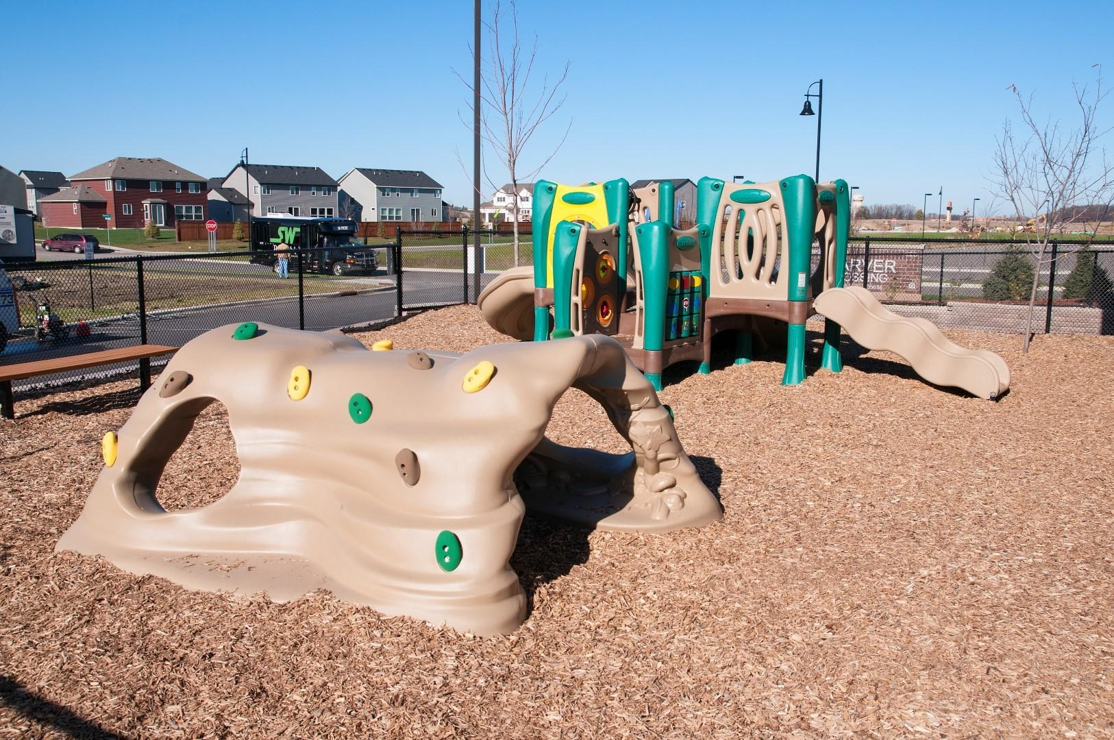 Playground Area with Wood-chips and Plastic Jungle Gym Sets at Carver Crossing Apartments