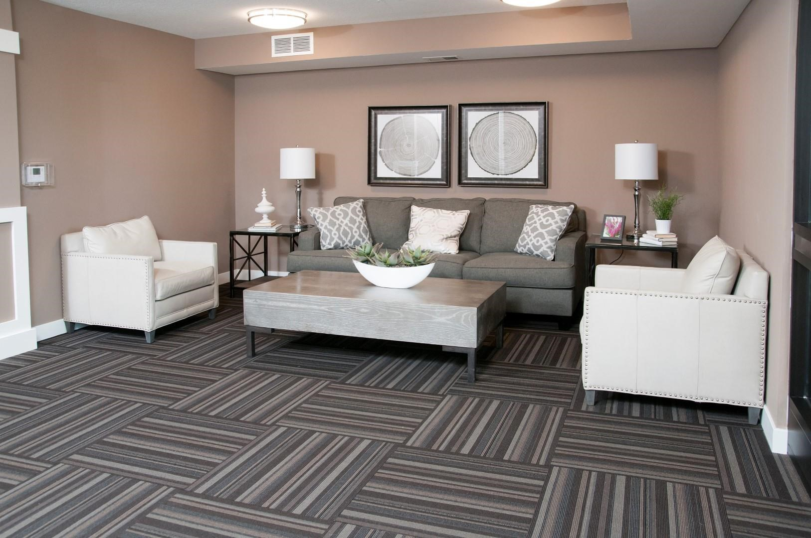Carver Crossing Lobby with Large Grey Couch and Two White Leather Chairs