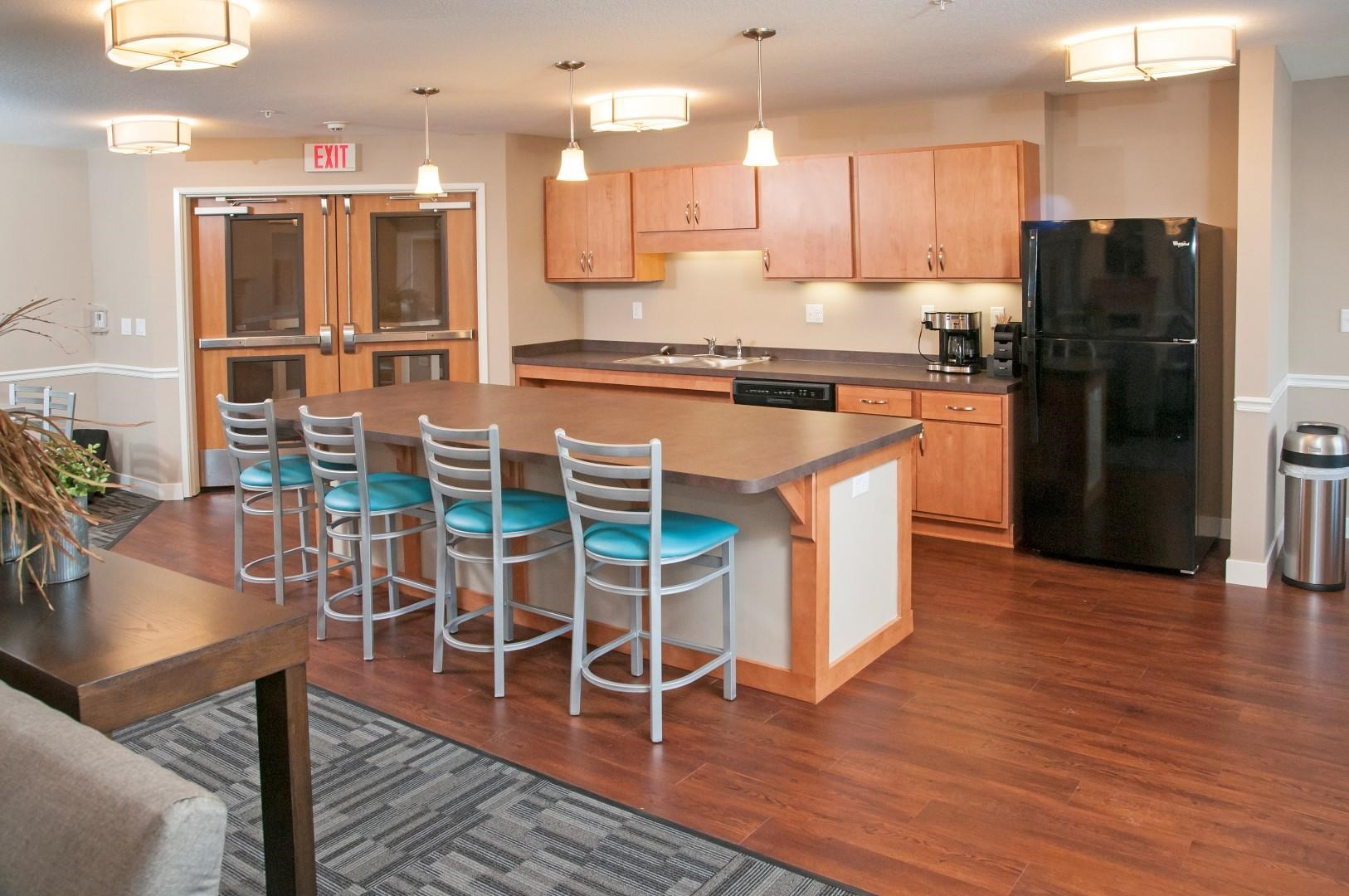 Kitchen with Full Sized Refrigerator, Dishwasher and Sink in Community Room of Apartments in Carver, MN