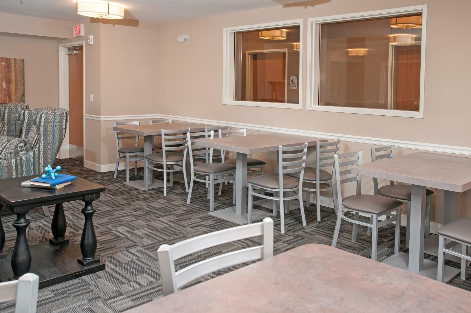 Multiple Small Tables with Chairs for Dining in Community Room in Carver, MN Apartments