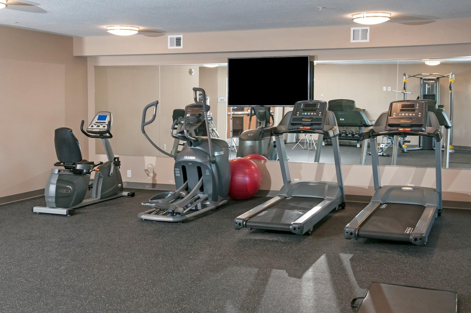 Fitness Room at Carver Crossing with Wall Length Mirrors and Flat Screen Television