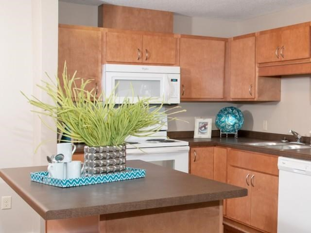Carver Crossing Apartment Kitchen with Medium Wood Cabinetry and Large Center Island