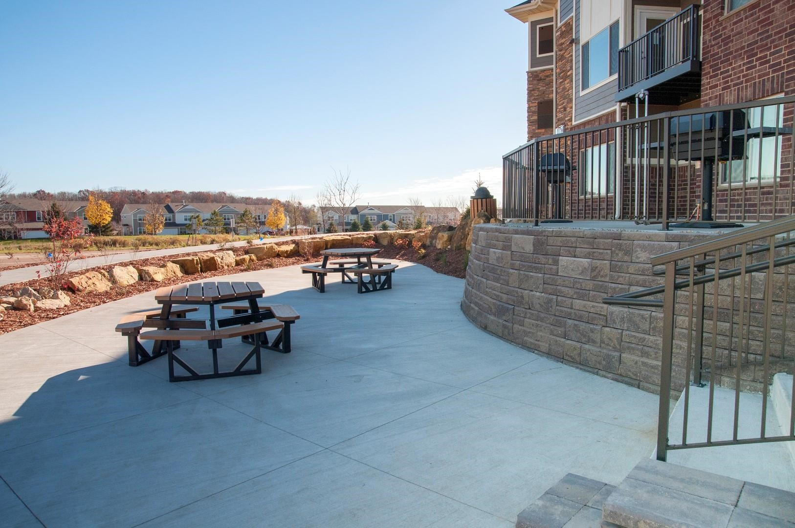 Large Concrete Patio in Back Exterior of Property in Carver, MN with Picnic Tables and Grilling Stations