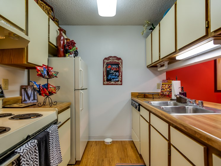 Kitchen with refrigerator, stove, garbage disposal and dishwasher at The Retreat at Woodridge Apartments in Lenexa, KS