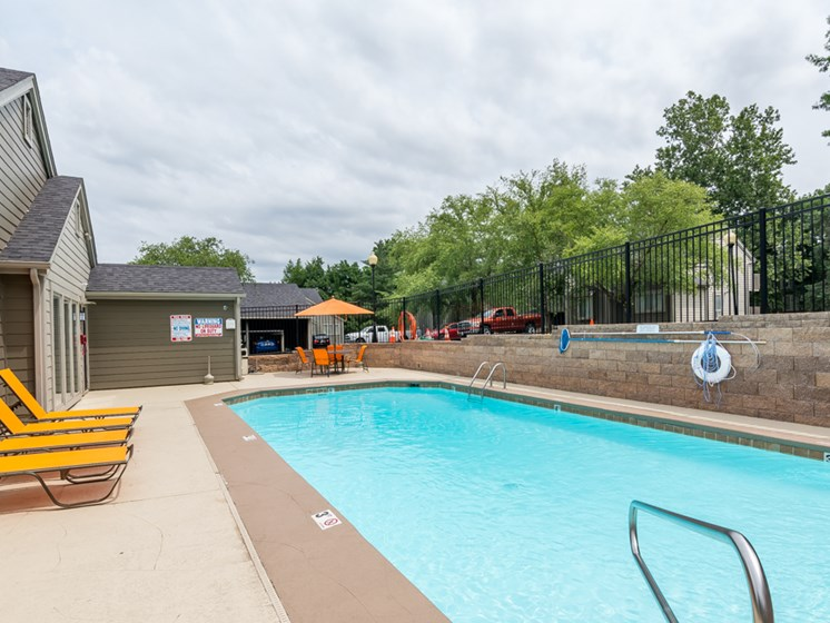 Sparkling blue pool with tanning chairs at The Retreat at Woodlands Apartments in South Kansas City, MO