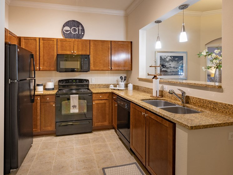 U shaped kitchen with black appliances and dark brown cabinets. Granite counter tops throughout the kitchen.