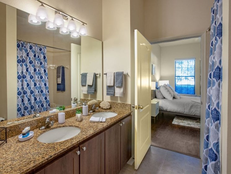 Bathroom with double vanity sinks pictured. Cabinets are dark brown with granite counter tops. Bathroom entry located within one of the bedroom.