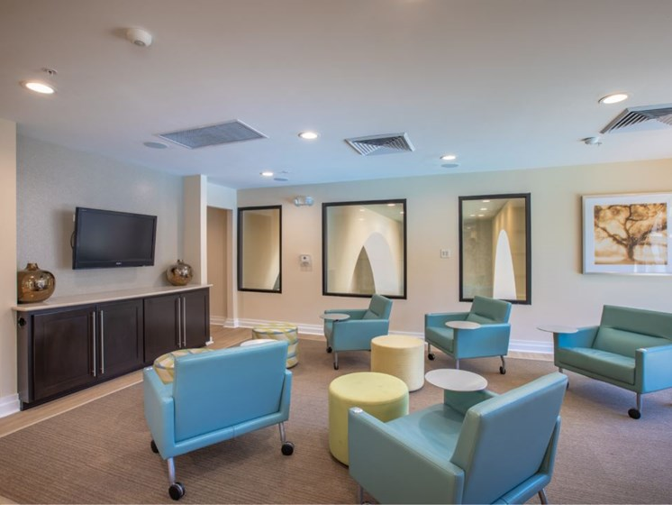 5 rolling desk chairs seating area facing TV located in the 2nd story of the Clubhouse.