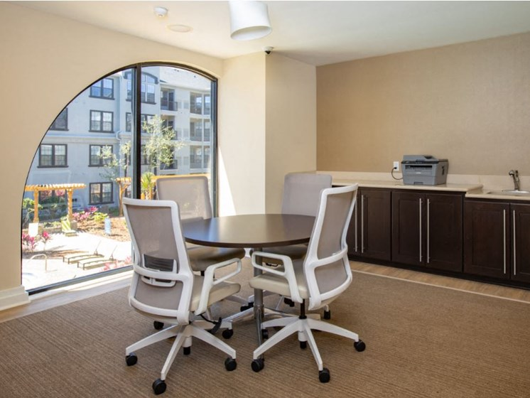 Round table with 4 computer desk chairs and printer located on top of counter. Located on the 2nd floor of Clubhouse.