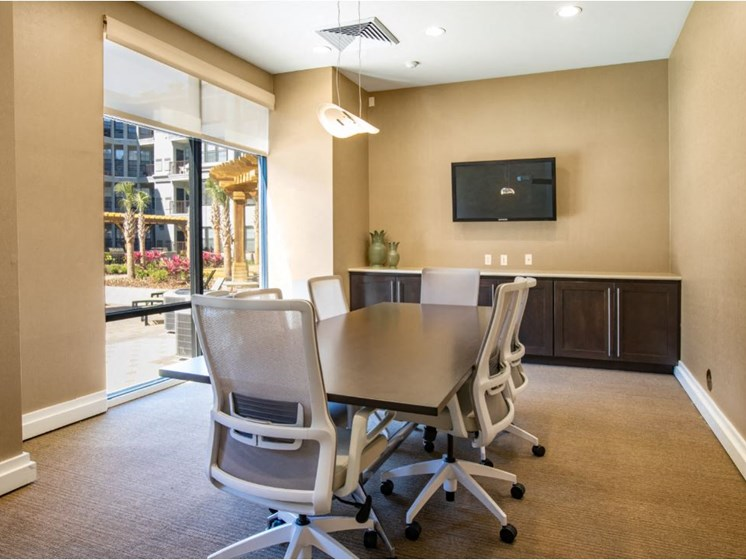 Business center with conference table with chairs and TV & printer.