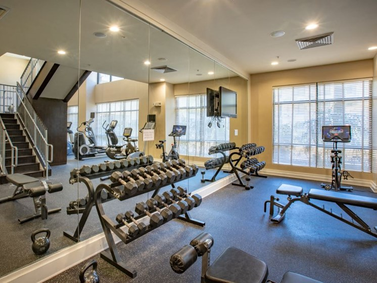Weight room with benches and peloton bicycle.