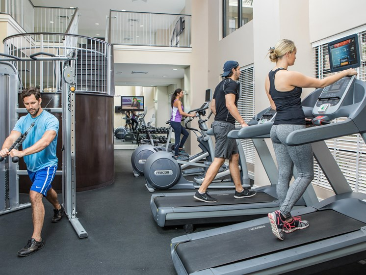 Fitness center with treadmills and lat pull machine. People running on treadmill and using stationary bicycle.