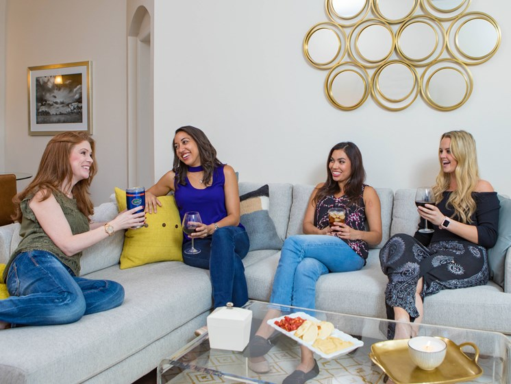 4 girls chatting and drinking wine while sitting on the couch.