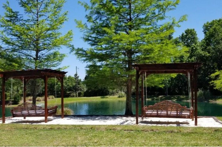 2 Pergola swing beds located on top of sand box located near the pond.
