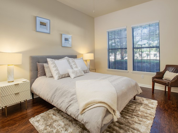 Bedroom pictured with full size bed, 2 night stands and accent chair in the far right corner.