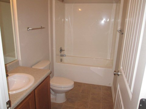 large bathroom with tub, toilet, and bathroom