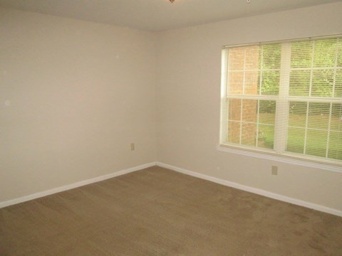 carpeted bedroom with large windows
