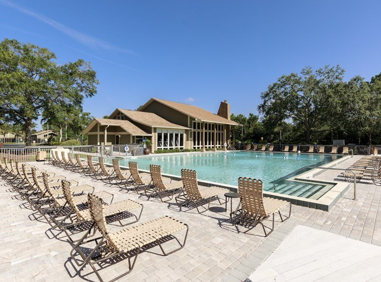 Large sundeck by pool with many lounge chairs