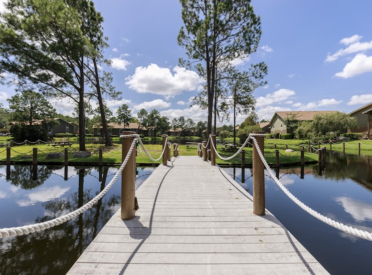 Bridge leading to BBQ island with grills and picnic tables