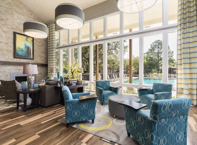 Clubhouse with ample seating and floor to ceiling windows overlooking pool